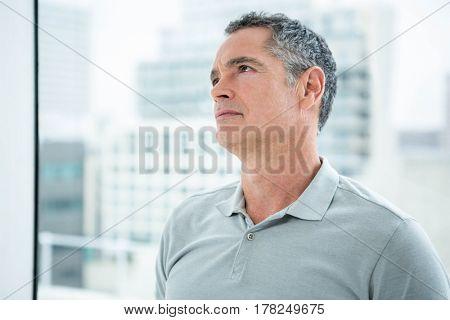 Tensed man standing against window and looking away