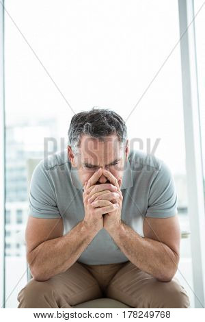 Tensed man sitting on chair and thinking against window