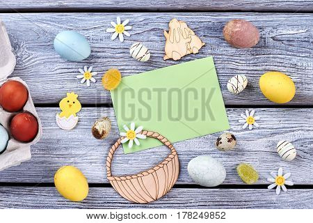Colored eggs and plywood figurines. Paper card and candies. Compilation of traditional Easter items.