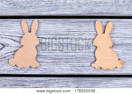 Wooden bunnies on grey background. Cutout animal figurines. Animalistic elements of decor.