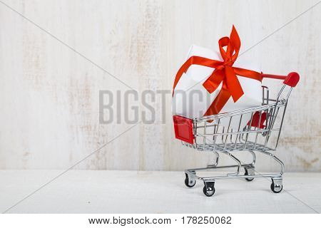 Shopping Cart With Gift Box On A Light Wooden Background.