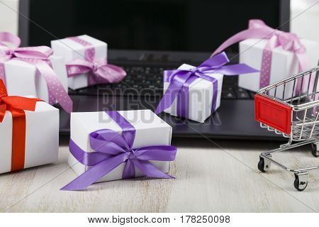 Shopping Cart And Many Gift Boxes On A Laptop.
