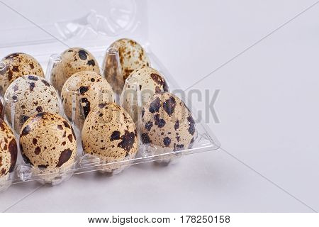 Quail eggs in plastic tray. Eggs on white background. What to eat on diet.