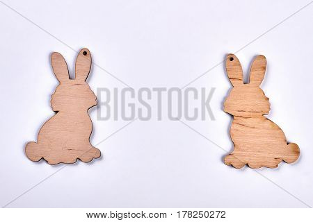 Two plywood rabbit cutouts. Plywood art on white background. Cute Easter souvenirs.