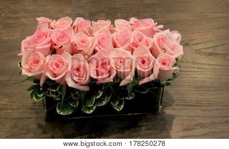 Horizontal image of closely trimmed roses placed neatly in long, rectangular vase