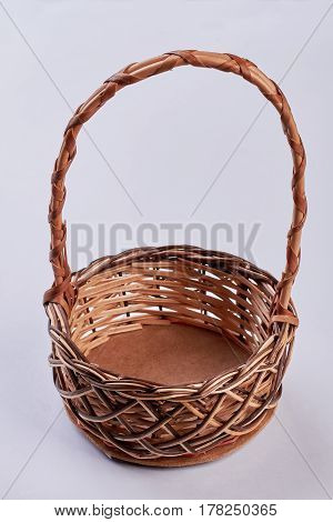 Wicker basket on white background. Basket with long handle. Buy handicraft items.