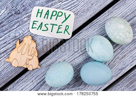 Dyed eggs on grey wood. Greeting card and plywood bunnies. Easter congratulatory composition.