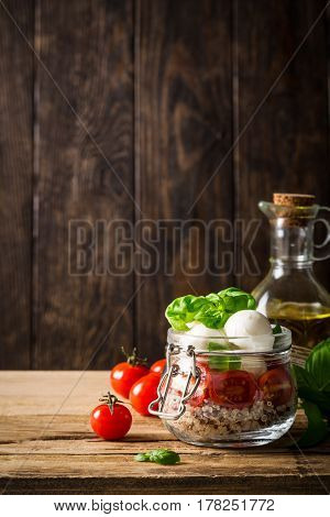 Delicious caprese salad with quinoa, ripe cherry tomatoes and mini mozzarella cheese with fresh basil leaves in glass jar and olive oil. Italian healthy food concept with copy space. Gluten free.