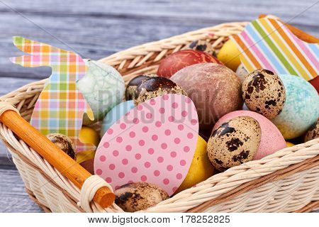 Easter basket close up. Colored eggs and paper cutouts. Traditions and art.