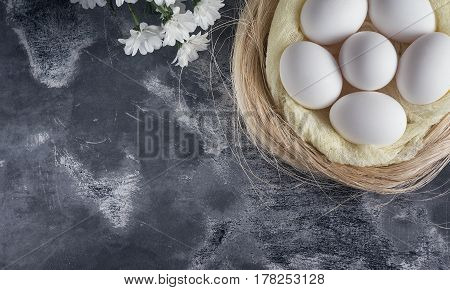 White Chicken Eggs In Easter Nest On Gray Background. Top View, Copy Space For Text