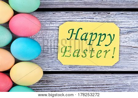 Happy Easter card, bright eggs. Yellow greeting card on wood. Christian traditions and holidays.
