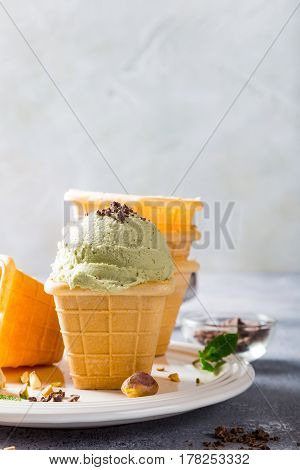 Pistachio ice cream with grated chocolate in waffle cups on gray stone background. Homemade summer food concept with copy space.