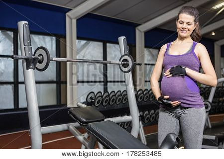 Smiling pregnant woman standing next to bench at the gym