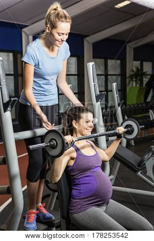 Smiling trainer helping pregnant woman lifting barbell at the gym