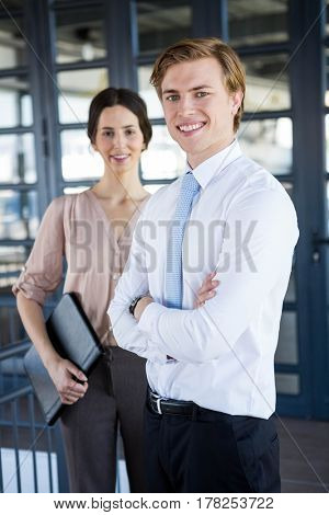 Portrait of businessman and businesswoman standing in office