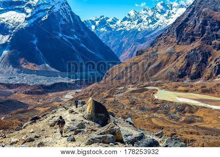 Mountain Valley View and Group of People walking on Trek carrying Backpacks using trekking Sticks dressed in alpine Jackets and hiking Pants