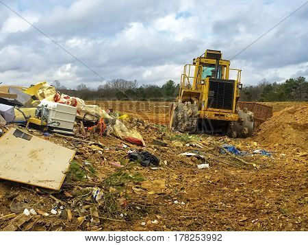 View of trash and heavy moving equipment at a dump site.