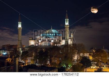Night View of Istanbul Downtown and Sophia Cathedral illuminated with spotlights and large full Moon in dark cloudy Sky