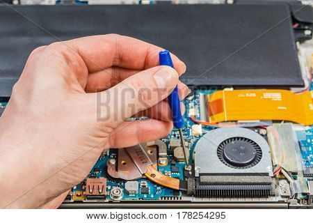 Person Hands Repairing Laptop Motherboard With A Screwdriver