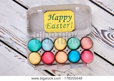 Egg tray, happy Easter card. Two rows of bright eggs. Healthy easter ideas.