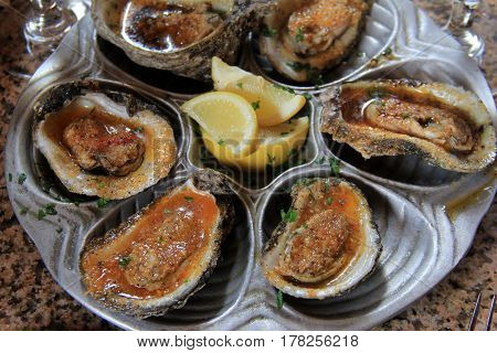 Large metal tray displaying six delicious baked oysters, drenched in butter  and seasonings.