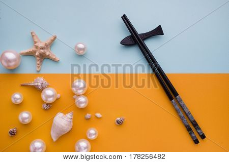 Japanese Sushi Chopsticks On Colored Background. Top View With Copy Space And Pearls And Seashells