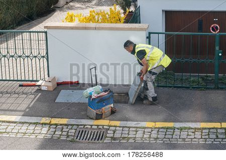 PARIS FRANCE - MAR 24 2017: Worker opening the sewage hole - telecomunication internet provider company working on implementation of fiber optic cables in sewage system - aerial view