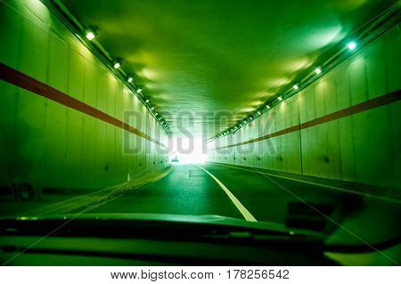 Moving fast on highway tunnel illuminated with green light