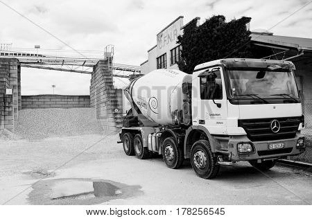STRASBOURG FRANCE - JUN 19 2016: Black and white of Mercedes-Benz Actros concrete truck from UNIBETON factory member of Italcementi Group in front of modern Beton Concrete Factory on a summer day