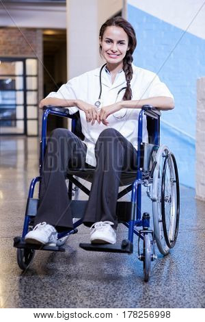 Portrait of happy female doctor sitting on wheel chair in hospital