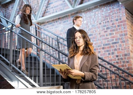 Businesswoman standing near staircase with documents in office