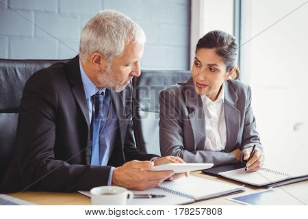 Businessman and businesswoman interacting in conference room