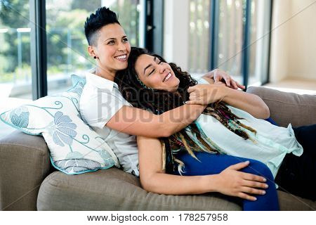 Smiling lesbian couple embracing and relaxing on sofa in living room