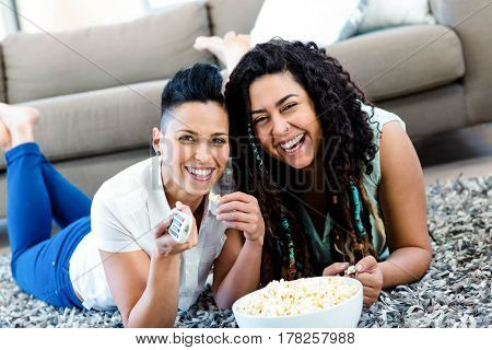 Lesbian couple lying on rug with a bowl of popcorn and watching television