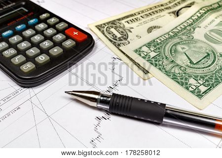 Fragment of electronic calculator with ball pen and US dollars banknotes on the background of currency growth schedule