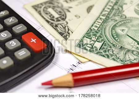 Fragment of electronic calculator US dollars banknotes and red pencil. Focus at the corner of a banknote