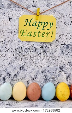 Row of painted Easter eggs. Greeting card, rope and clothespin.