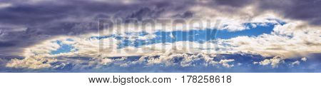 background panorama. clear blue sky and sunlight are visible through dramatic storm clouds