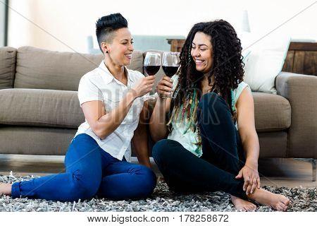 Lesbian couple sitting on rug and toasting wine glasses
