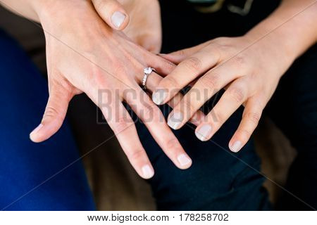 Close-up of womans hand putting a ring on her partners finger