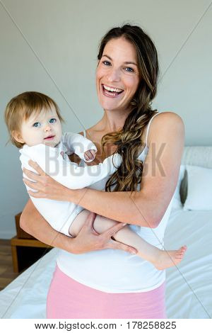 smiling brunette woman is holding a cute baby while sitting on a bed