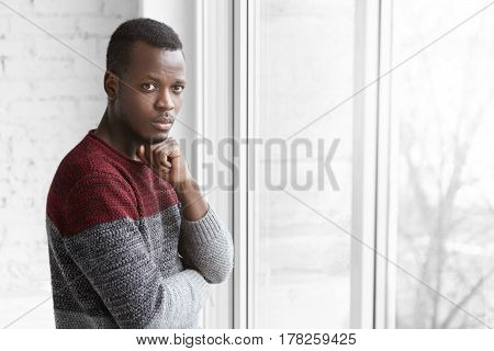 Indoor Shot Of Young Dark-skinned Man Dressed Casually Holding Hand On His Chin Feeing Worried Befor