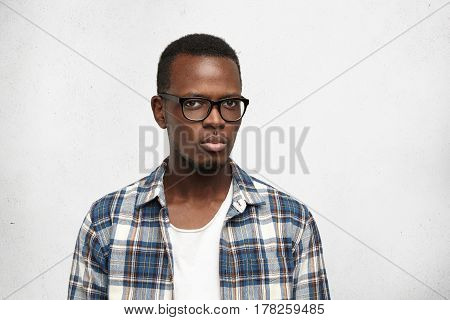 Studio Shot Of Suspicious Young African American Hipster Wearing Stylish Glasses Frowning, Looking A
