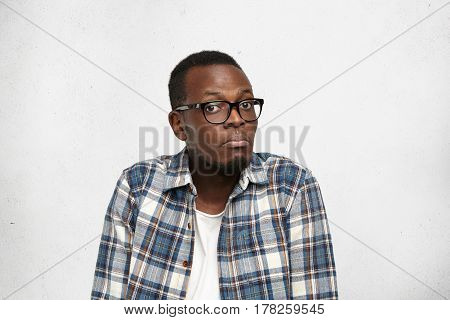 Human Emotions And Feelings. Doubtful Expression. Dark-skinned Male In Glasses Sitting And Shrugging