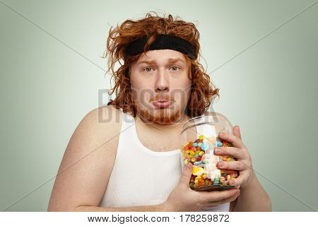 Portrait Of Funny Overweight Young Redhead Male With Sports Band On His Head Having Unhappy And Sad