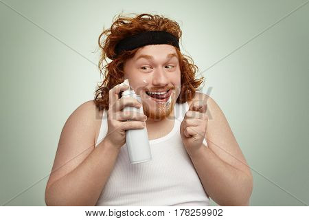 Sly Redhead Fat Male In Sports Band And Tank Top Holding Spray Can, Having Crazy Joyful Look, Lickin