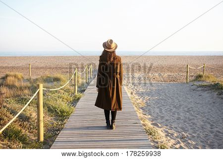Back View Of Brunette Girl In Hat And Coat Standing On Boardwalk By Seaside, Contemplating Beautiful