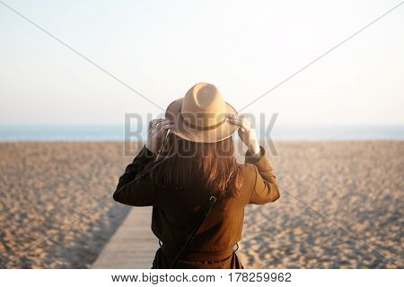Back View Of Unrecognizable Young Brunette Woman Dressed In Overclothes Adjusting Her Stylish Hat Wh