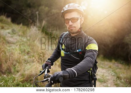 Outdoor Shot Of Handsome Young Professional Mountain Biker In Helmet, Glasses And Leather Gloves Sta