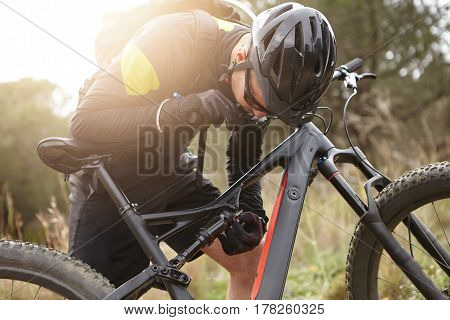 Candid View Of Male Cyclist In Sportswear, Protective Helmet And Glasses Fixing His Motor-powered El